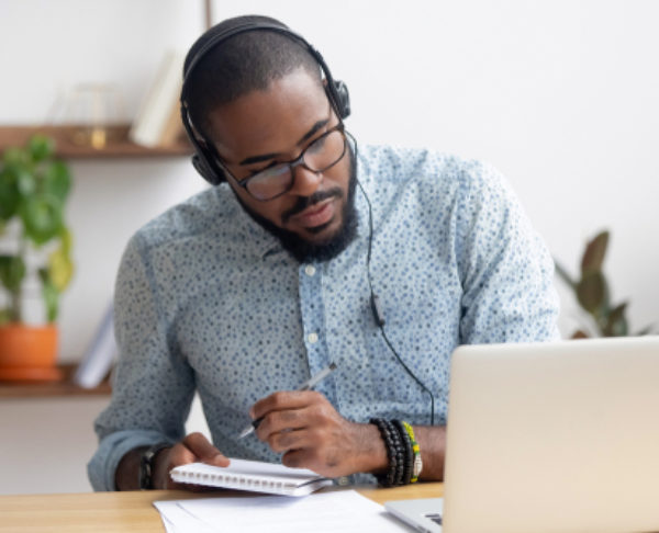 Focused,African,Business,Man,In,Headphones,Writing,Notes,In,Notebook